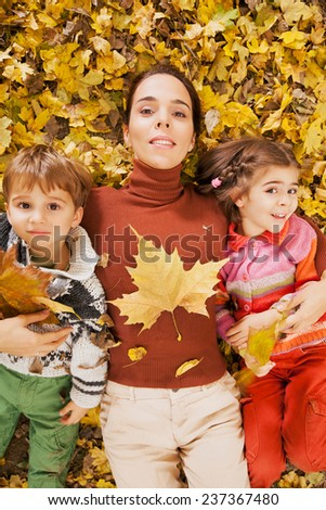 Family playing with autumn leaves in nature - stock photo