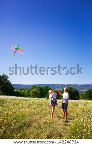 Family playing with kite on the flower meadow