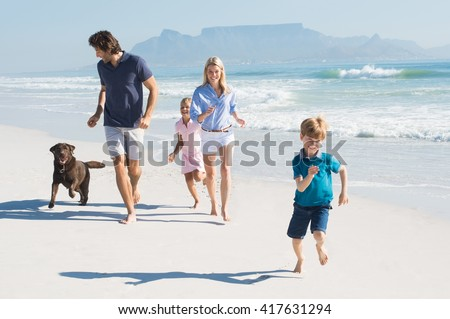 Family playing with pet on the beach. Happy beautiful family running at beach with pet dog. Smiling parents with son and daughter having fun at seaside. - stock photo