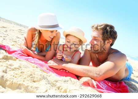 Family playing with seashells on the beach - stock photo