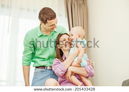 Family playing with the child together (focus on the eyes of baby) - stock photo