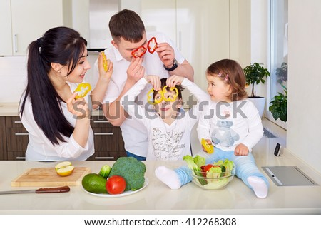 Family playing with vegetables in kitchen - stock photo
