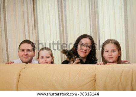 Family portrait at home behind sofa - with two children and dog - stock photo