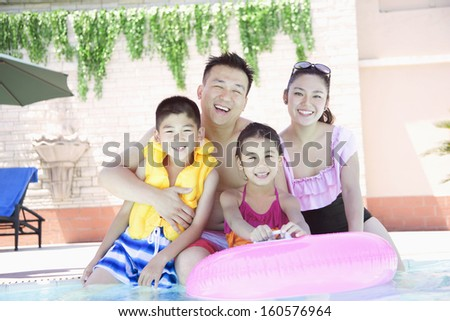 Family portrait by the pool - stock photo