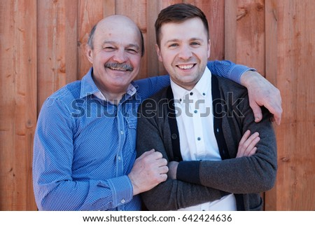 Family portrait. Father-in-law embraces the son-in-law. They are smiling at the camera.
