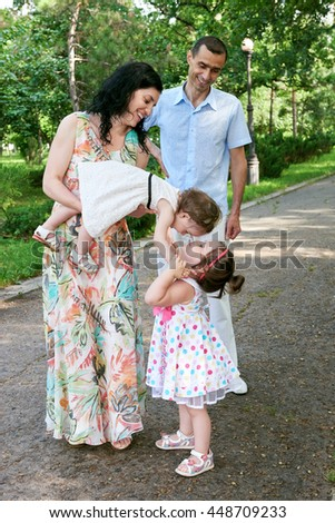 family portrait in summer city park, parents with child, summer season, green grass and trees