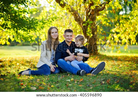 Family portrait in the nature - mother, father and little son sitting on the Sunny meadow under a branchy tree, grass, yellow leaves, early fall, full growth. - stock photo
