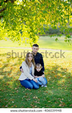 Family portrait in the nature - mother, father and son sit on the grass under a spreading tree, early warm spring, near the fallen yellow leaves, full growth.