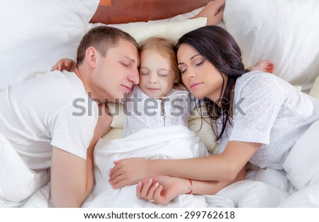 Family portrait laying in bed - stock photo