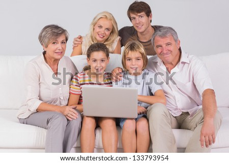 Family portrait looking at camera with a laptop in sitting room - stock photo