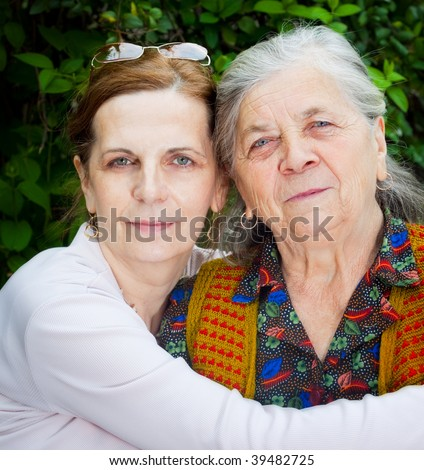 Family portrait - middle age daughter and senior mother - stock photo