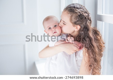 family portrait mother and daughter kissing and hugging white background