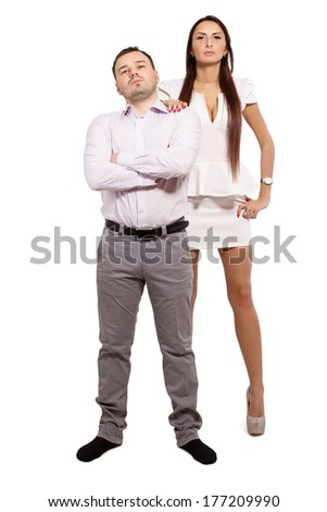Family portrait of a modern young people. Man and woman wear a dress code. Complex family relationships. Woman dominates man. Love and hate each other simultaneously. Distrust in family relations. - stock photo