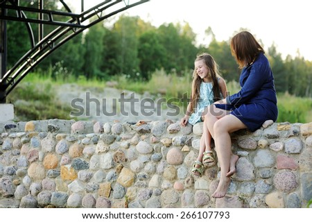 Family portrait of a smiling and cheerful mother and daughter having fun near th river