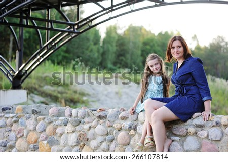 Family portrait of a smiling and cheerful mother and daughter having fun near th river - stock photo