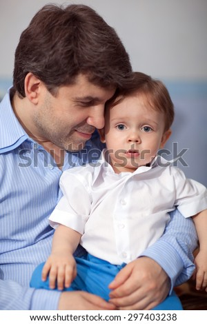 Family portrait of a young father holding lovely little son in his arms. Dad looking at the boy. Happy fatherhood