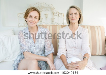 Family portrait of an adult daughter and her mature mother lounging together on a sofa in the garden at home, relaxing and being comfortable. - stock photo