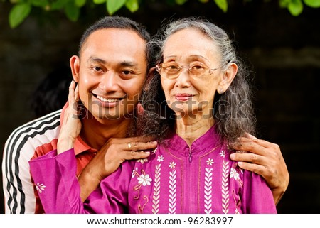 family portrait of asian ethnic senior woman with young adult son