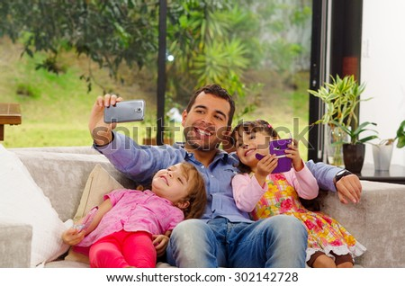 Family portrait of father and two daughters sitting together in sofa posing for selfie cozy family style. - stock photo