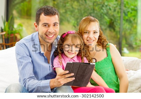 Family portrait of father , mother and daughter sitting together in sofa holding tablet looking towards camera. - stock photo