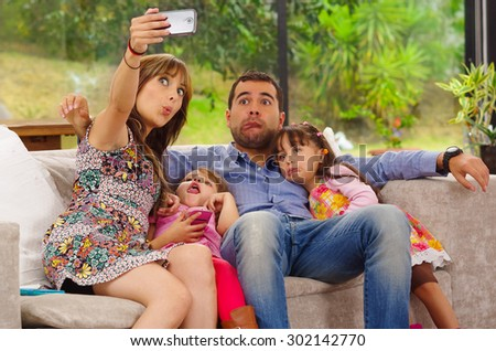 Family portrait of father, mother and two daughters sitting together in sofa posing for selfie making funny faces. - stock photo