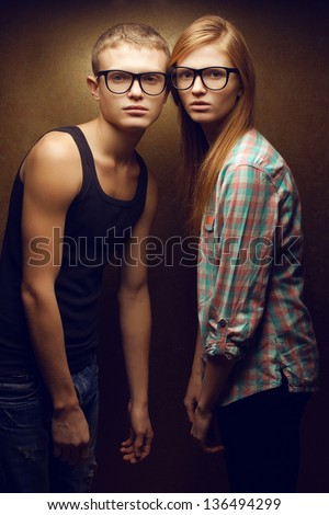 Family portrait of gorgeous red-haired fashion twins in casual shirts wearing trendy glasses and posing over golden background together. Hipster style. Studio shot.