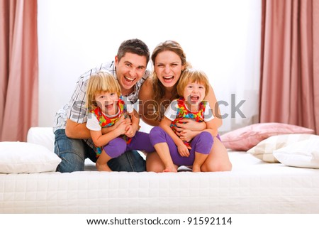 Family portrait of happy mom dad and twins daughters having fun time