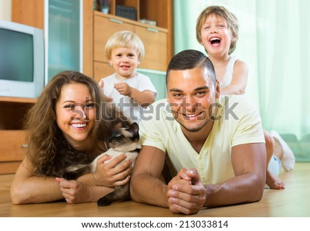 Family portrait of happy parents and two daughters with Siamese. Focus on man  - stock photo