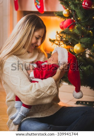 Family portrait of mother and baby boy sitting at Christmas fireplace - stock photo