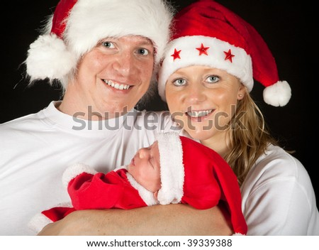 Family portrait of newborn baby with parents and santa hats - stock photo