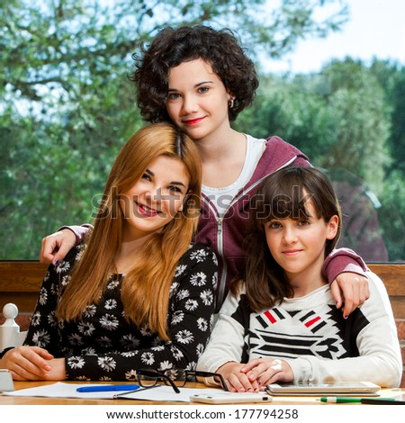 Family portrait of three adolescent sisters together at desk. - stock photo