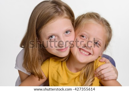 Family portrait of two sisters embracing each other. The elder girl looks right in the camera with amazing blue eyes, the other child smiles and looks aside.
