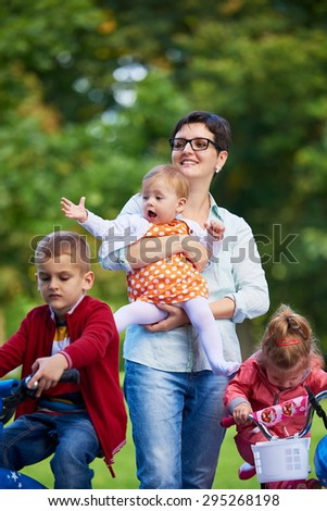 Family portrait outdoor in park. Modern mom with kids. Child learning to ride bike - stock photo