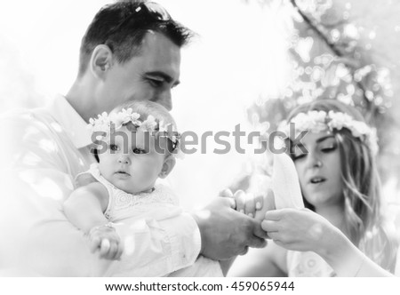 Family portrait outdoors. Baby girl and her parents. Sunny Summer day Family Picnic. Happy family concept. Beautiful kid playing outside with parents.Young couple spending time on a summer day - stock photo