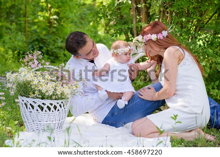 Family portrait outdoors picnic. Baby girl and her parents. Sunny Summer day Family Picnic. Happy family concept. Beautiful kid playing outside with parents.Young family spending time on a summer day - stock photo