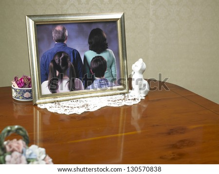 family portrait photograph with the family turned away from the viewer on a wooden table surface and ornaments to suggest an old person's house - stock photo