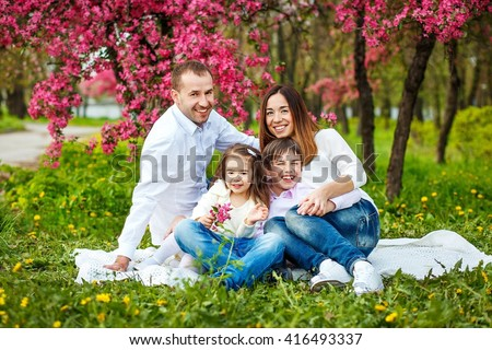 Family portrait photography. Family are smiling and looking at the camera. They are dressed in a blue jeans and light shirts.They hug and smile. Spring,