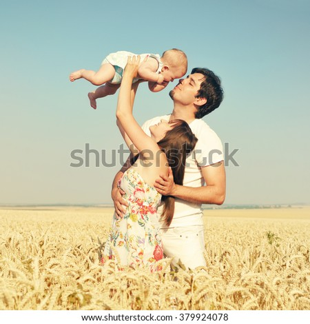 Family portrait. Picture of happy loving father, mother and their baby outdoors. Daddy, mom and child against summer blue sky. - stock photo