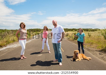 Family poses for a photo on a quiet road in the country - stock photo