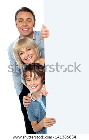 Family posing from behind blank white ad board - stock photo