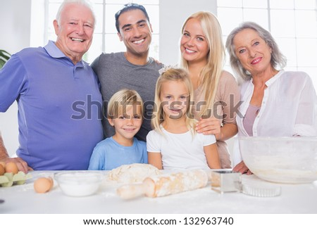 Family posing in the kitchen in front of kitchen utensils - stock photo