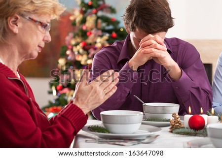 Family praying at the table before  chritmas dinner - stock photo