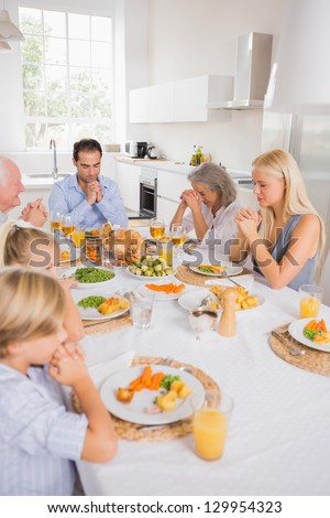 Family praying before eating for thanksgiving