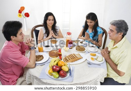Family praying before having breakfast