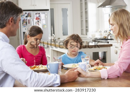 Family Praying Before Having Meal In Kitchen Together - stock photo