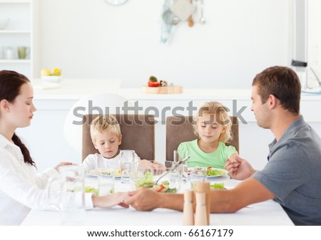Family praying together before eating their salad for lunch in the kitchen