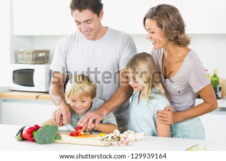 Family preparing vegetables together in the kitchen - stock photo