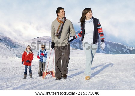 Family pulling sled in snow - stock photo