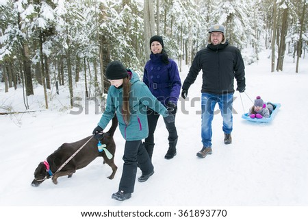 Family Pulling Sledge Through Snowy Landscape - stock photo