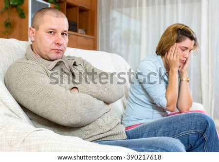 Family quarrel. Sad man and crying adult woman at home - stock photo